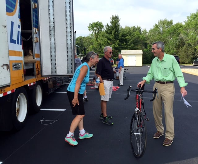Anchor House cyclist Mark Smith shares a laugh with ride Barb Keener before loading his bike on a truck headed for Manchester, New Hampshire.